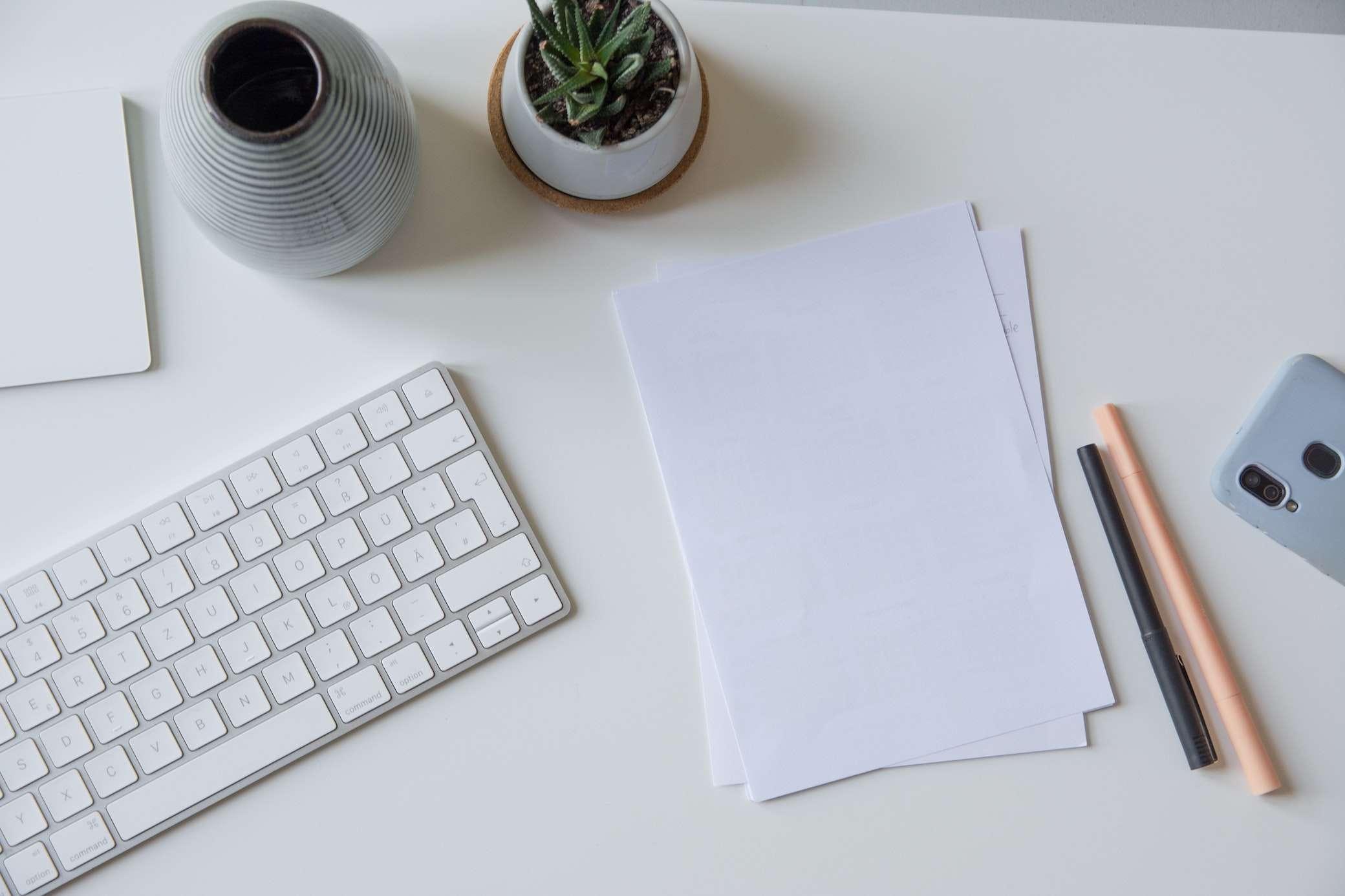 Schreibtisch mit Papier und Tastatur